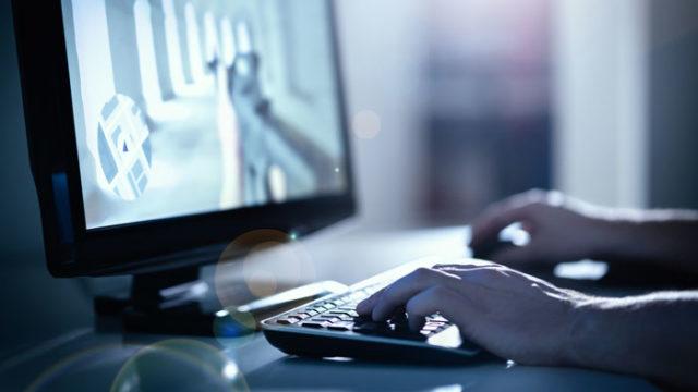 パソコンでFPSゲームを楽しむ男性